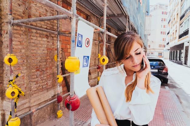 Geschäftsfrau talkin am telefon mit gerüst im hintergrund