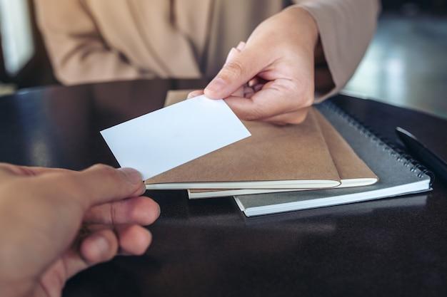 Geschäftsfrau tauscht visitenkarte mit notizbüchern auf tisch im büro aus