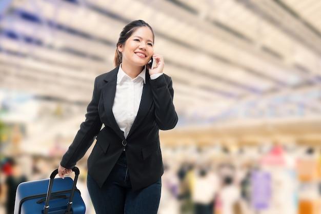 Geschäftsfrau telefoniert mit dem handy beim tragen von gepäck im flughafen