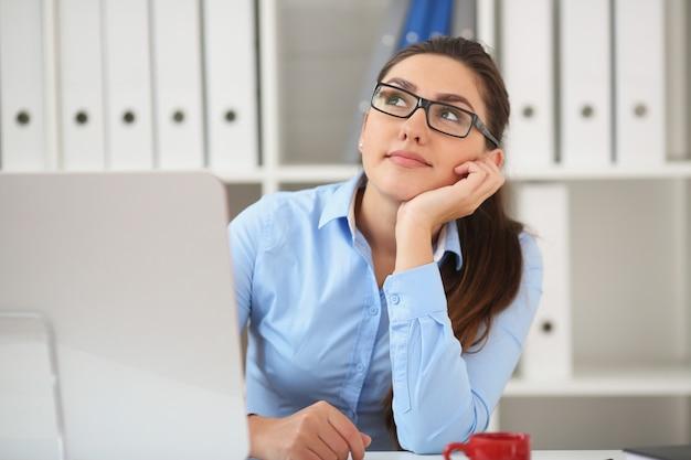 Geschäftsfrau träume. im büro am tisch sitzen