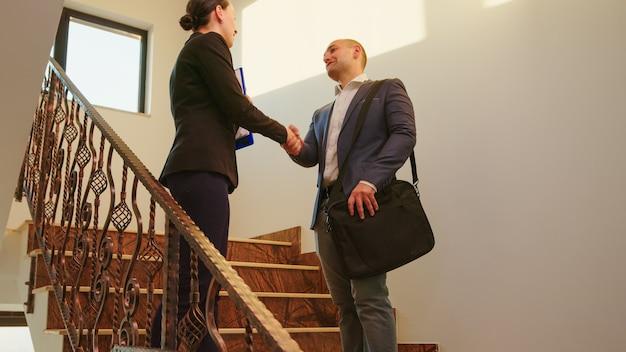 Geschäftsfrau trifft mann kollegen im firmenbüro gruß mit handschlag begrüßen und sprechen auf treppen. team von professionellen geschäftsleuten, die im modernen finanzgebäudegruß arbeiten.