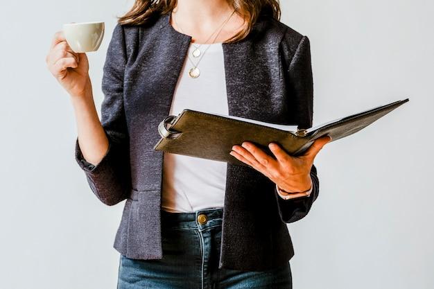 Geschäftsfrau trinkt eine tasse kaffee, während sie ihre agenda überprüft