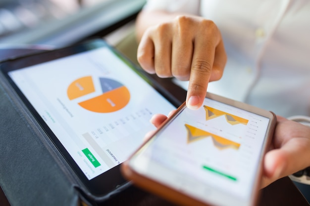 Geschäftsfrau überprüfen daten in smartphone und tablet