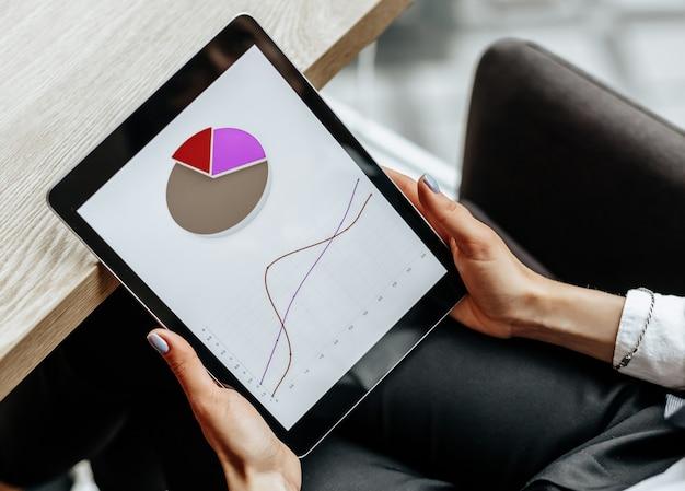 Geschäftsfrau überprüft diagramme und aktualisiert den finanziellen fortschritt. das mädchen analysiert das geschäftsmodell am arbeitsplatz.