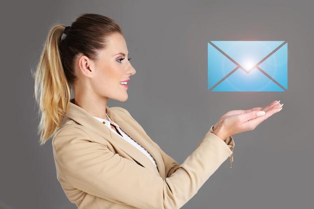 Geschäftsfrau und e-mail-zeichen auf grauem hintergrund