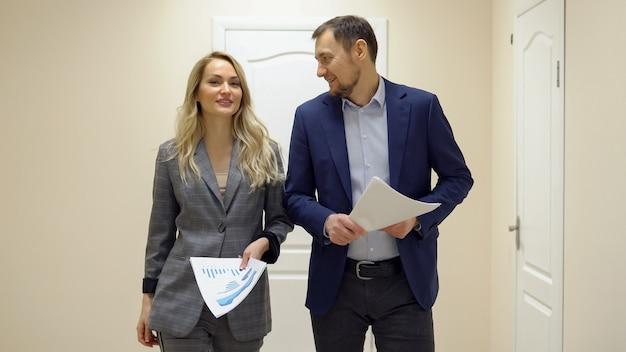 Geschäftsfrau und ein mann gehen den flur entlang und unterhalten sich