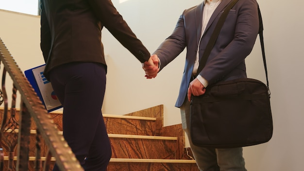 Geschäftsfrau und geschäftsführender manager, die sich die hände schütteln, während sie auf der treppe stehen und im bürogebäude diskutieren. gruppe professioneller geschäftsleute, die an einem modernen finanzarbeitsplatz arbeiten.