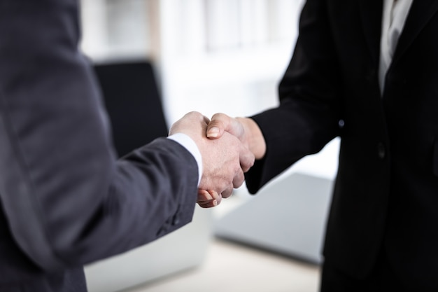 Geschäftsfrau und geschäftsmann, die hände schütteln im hintergrund des büroraums, nachdem der vertrag unterzeichnet oder der handshake-begrüßungsvertrag unterzeichnet wurde, drückte das geschäft das vertrauen aus und stärkte das erfolgreiche konzept