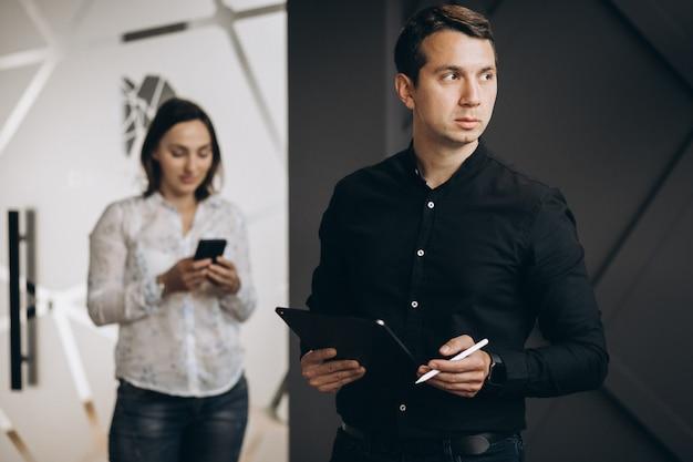 Geschäftsfrau und geschäftsmannkollegen arbeiten am laptop