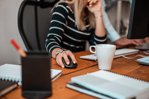 Geschäftsfrau und kollege, die an ihrem schreibtisch im büro arbeiten.