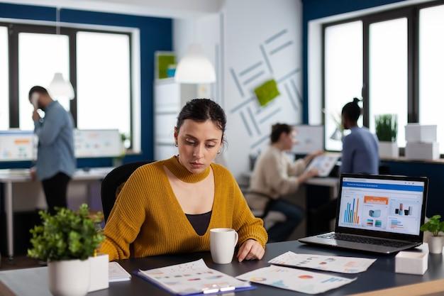 Geschäftsfrau und managementteam, die mit firmendiagrammen an dokumenten arbeiten