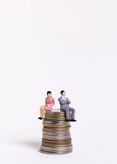 Geschäftsfrau und mann, die auf einem stapel der vorderansicht der münzen sitzen