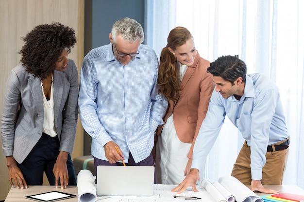 Geschäftsfrau und mitarbeiter diskutieren blaupause auf dem schreibtisch