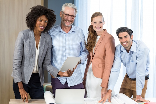 Geschäftsfrau und mitarbeiter mit blaupause auf dem schreibtisch