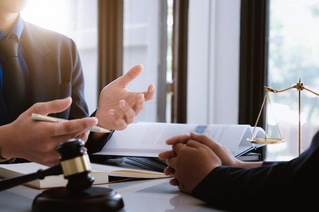 Geschäftsfrau und rechtsanwälte, die vertragspapiere mit messingskala auf hölzernem schreibtisch besprechen