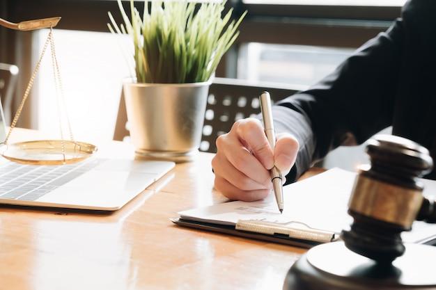 Geschäftsfrau und rechtsanwälte, die vertragspapiere mit messingskala auf hölzernem schreibtisch im büro besprechen