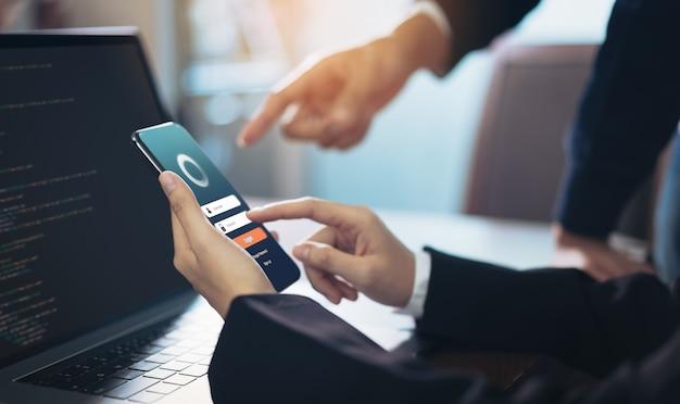 Geschäftsfrau und team entwerfen anwendungen auf dem smartphone