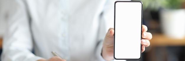 Geschäftsfrau unterschreibt vertrag und hält smartphone mit weißem bildschirm