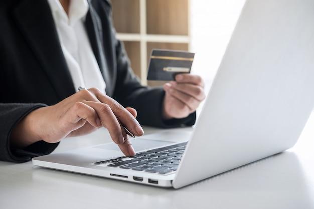 Geschäftsfrau-verbraucher, der kreditkarte hält und auf laptop für das on-line-einkaufen und die zahlung schreibt, schließen einen kauf im internet, on-line-zahlung, vernetzung ab und kaufen produkttechnologie