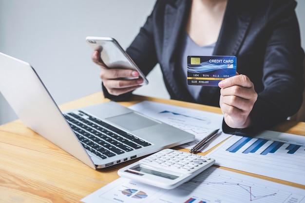 Geschäftsfrau-verbraucher, der smartphone, kreditkarte hält und auf laptop für das on-line-einkaufen und die zahlung schreibt, schließen einen kauf im internet, eine on-line-zahlung, eine vernetzung ab und kaufen produkttechnologie