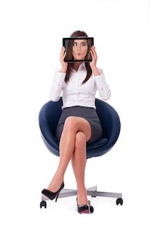 Geschäftsfrau versteckt sich hinter tablette, die lustiges gesicht anzeigt