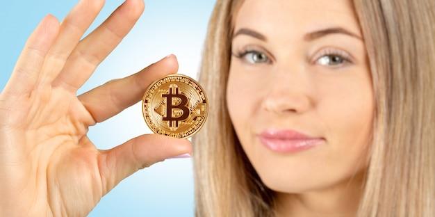 Geschäftsfrau, welche die bitcoin goldmünze anhält