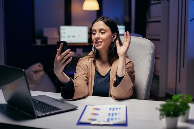 Geschäftsfrau winkt während des anrufs mit kollegen, die überstunden machen. frau, die während einer videokonferenz mit kollegen nachts im büro an finanzen arbeitet.