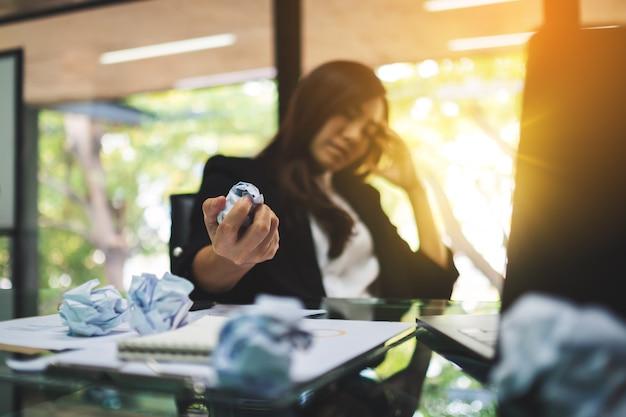 Geschäftsfrau wird gestresst, vermasselt papiere, während sie ein problem bei der arbeit im büro haben