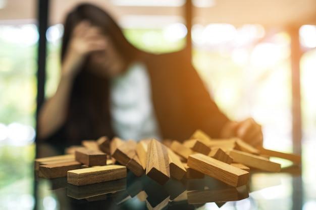 Geschäftsfrau wird gestresst, während sie ein problem bei der arbeit im büro mit holzklötzen des tumble tower-spiels auf dem tisch hat