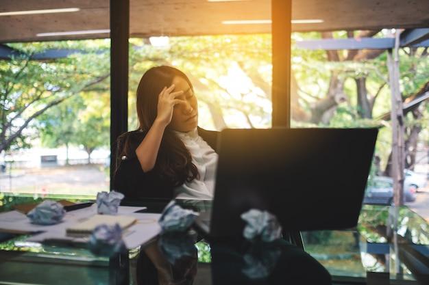 Geschäftsfrau wird mit vermasselten papieren und laptop auf dem tisch gestresst, während sie ein problem bei der arbeit im büro hat