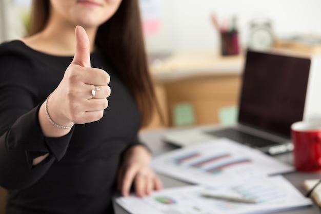 Geschäftsfrau zeigt daumen oben sitzend an ihrer büronahaufnahme. perfektes waren- oder servicequalitätskonzept