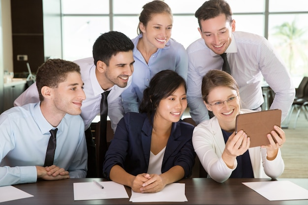 Geschäftsfrau zeigt tablet-pc zum team