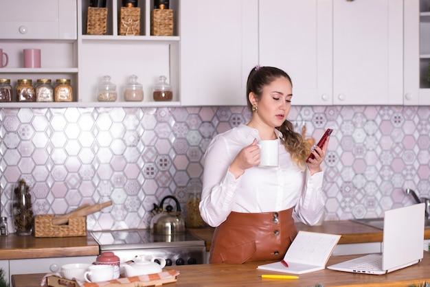 Geschäftsfrau zu hause in der küche löst geschäft am telefon arbeitet online