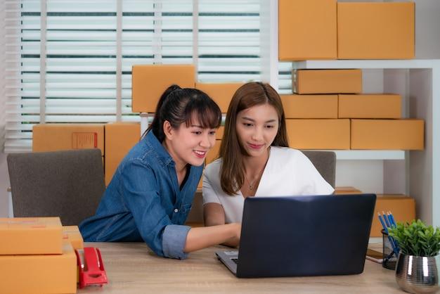 Geschäftsfrauarbeit mit zwei asiatische jugendlichinhabern, die auf dem tisch für das on-line-einkaufen, bestellung auf lieferungspostversand mit büroeinrichtung überprüfend, unternehmerlebensstilkonzept sitzt