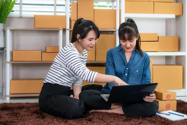 Geschäftsfrauarbeit mit zwei asiatische jugendlichinhabern, die im boden für das on-line-einkaufen, bestellung auf lieferungspostversand mit büroeinrichtung überprüfend, unternehmerlebensstilkonzept sitzt