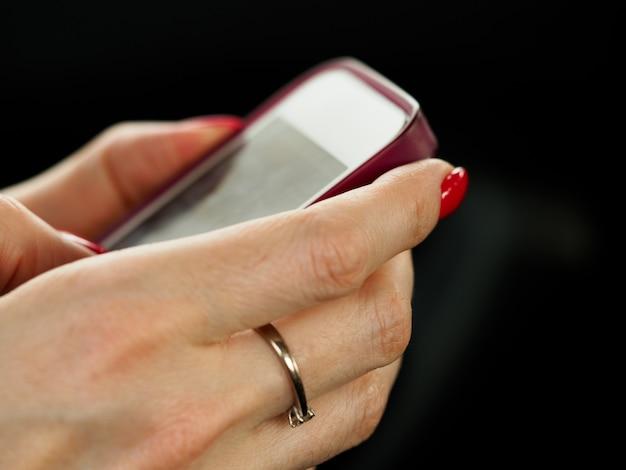 Geschäftsfrauarmgriff und gebrauchsmobiltelefonnahaufnahme