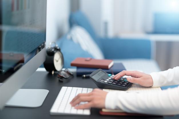 Geschäftsfrauen arbeiten mit taschenrechner- und computerdesktop auf moderner arbeitstabelle