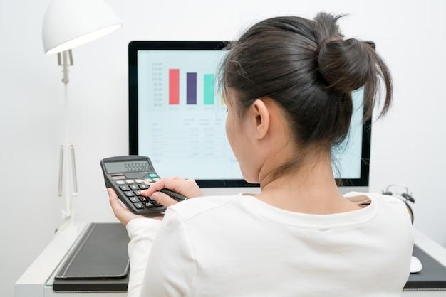 Geschäftsfrauen arbeiten mit taschenrechner- und computerdesktop und -stift