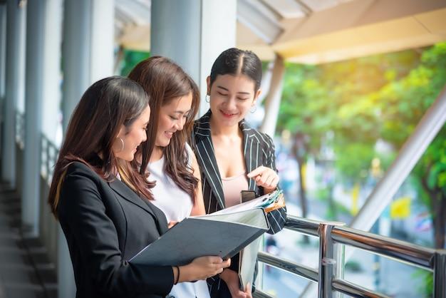 Geschäftsfrauen betrachten den bericht und sprechen miteinander