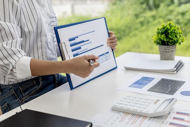 Geschäftsfrauen betrachten die finanzdokumente des unternehmens, um probleme zu analysieren und lösungen zu finden, bevor sie die informationen zu einem treffen mit einem partner bringen. finanzielles konzept.