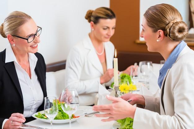 Geschäftsfrauen, die am geschäftsessen sich treffen