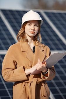 Geschäftsfrauen, die an der überprüfung von geräten im solarkraftwerk arbeiten. mit tablet-checkliste arbeitet frau im freien an solarenergie.