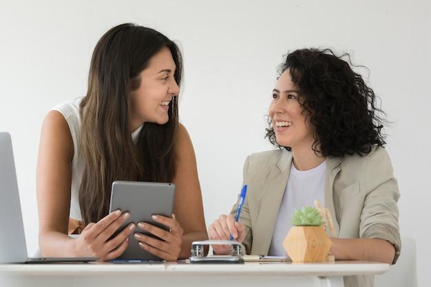 Geschäftsfrauen, die an einander lächeln
