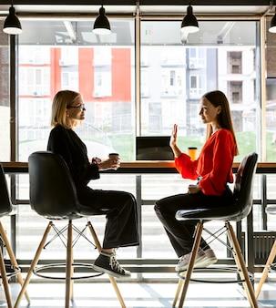 Geschäftsfrauen, die bei der arbeit gebärdensprache verwenden, um miteinander zu sprechen