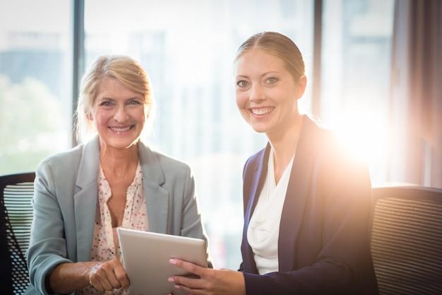 Geschäftsfrauen, die digitales tablett halten
