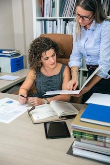 Geschäftsfrauen, die dokumente im ordner im büro suchen. weibliches unternehmensführungskonzept.