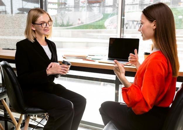 Geschäftsfrauen, die gebärdensprache bei der arbeit verwenden, um zu kommunizieren