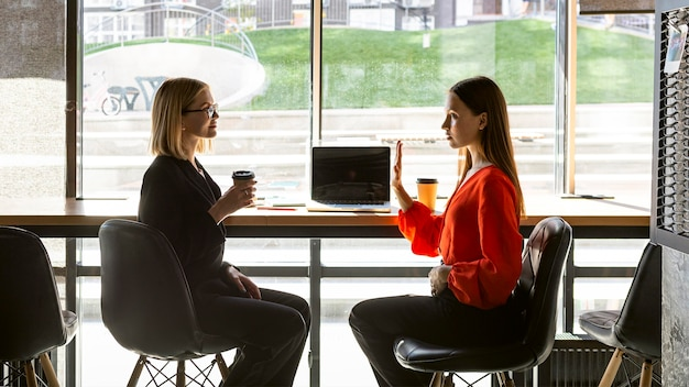 Geschäftsfrauen, die gebärdensprache bei der arbeit verwenden