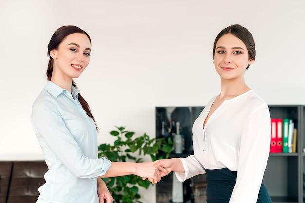 Geschäftsfrauen, die im büro zusammenarbeiten und hände auf einem abkommen rütteln