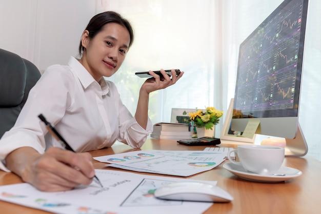 Geschäftsfrauen, die smartphone halten, um mit lautsprechertelefon zu sprechen und notizen auf schreibtisch im büro zu machen. geschäftsleute fordern die zusammenarbeit mit kunden oder partnern mit smartphones. unternehmenskonzept.